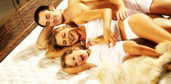 Семья лежит на матрасе